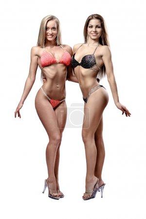 Foto de Dos hermosa chica atlética usar bikini posando sobre fondo blanco - Imagen libre de derechos