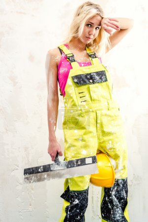 Tired female construction worker with putty knife working indoors