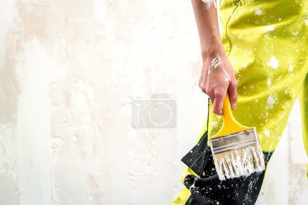 Female hand with paint brush over white obsolete background