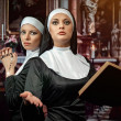 Two attractive young nuns with rosary and bible pr...