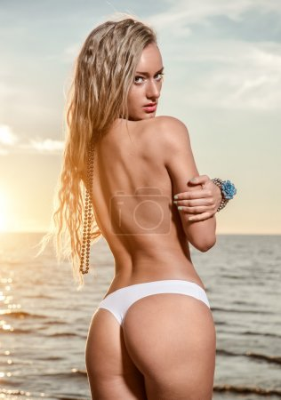Sexy young woman with long hair posing on the beach at sunset