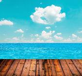 Blue ocean and sky above wood plank floor