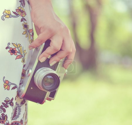 Woman hand holding retro camera close-up