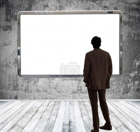 Man in gallery room looking at huge empty billboard