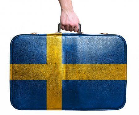 Tourist hand holding vintage leather travel bag with flag of Swe