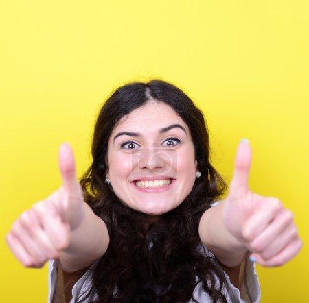 Photo pour Portrait de femme heureuse avec les pouces vers le haut contre fond jaune - image libre de droit