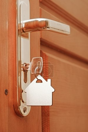 Photo for House key on a house shaped keyring in the lock of a door - Royalty Free Image