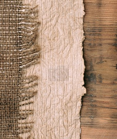 Old paper with natural burlap on wooden backround