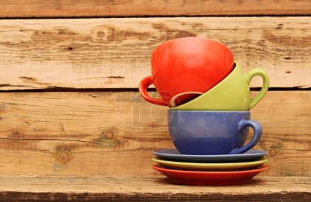 Photo for Colorful coffee mugs over an grunge wooden background - Royalty Free Image