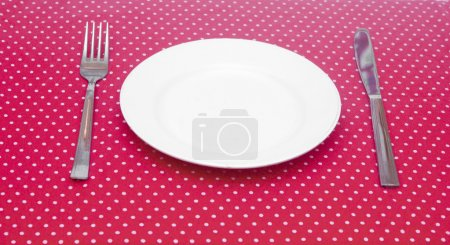 Empty white dinner plate with utensils on fun red polka dot tabl