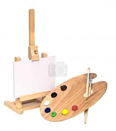 Foto de Caballete de madera con papel limpio y paleta de artistas de madera cargado con varias pinturas de color y pincel, aislado sobre un fondo blanco - Imagen libre de derechos