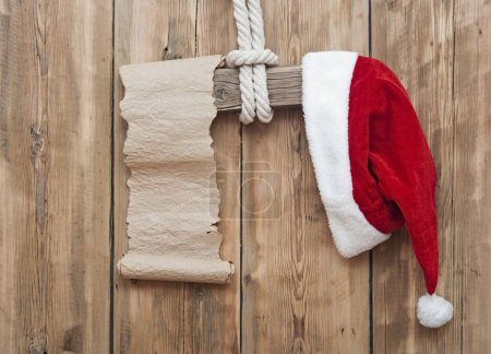 Wooden sign with Santa's hat and blank paper scroll on a wooden