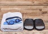 Brýle na plavání a ručník na dřevěné pozadí