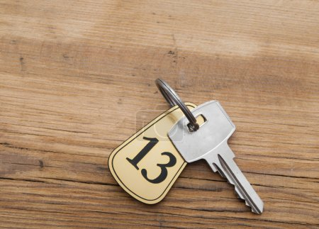 Photo for Closeup of an key of room number 13 with key on a wooden desk - Royalty Free Image