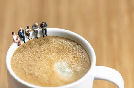 Miniatur-Business-Team bei einer Kaffeepause