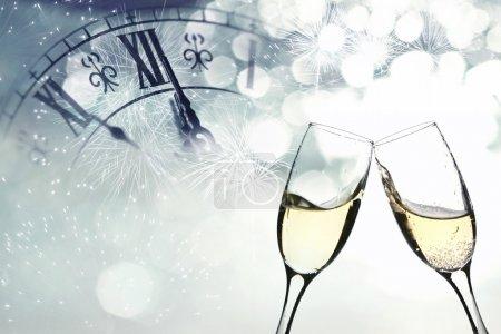 Photo pour Verres avec champagne contre feux d'artifice et horloge vers minuit - image libre de droit