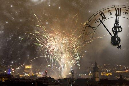 Photo pour Vacances feux d'artifice et horloge vers minuit sur la ville - image libre de droit