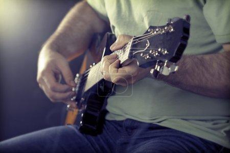 Photo pour Gros plan homme jouant à la guitare est studio - image libre de droit