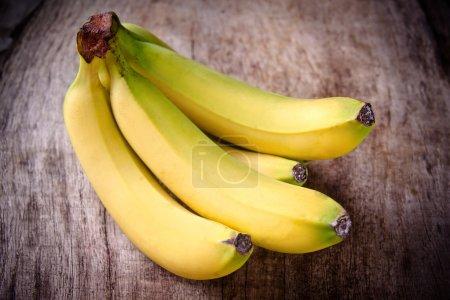 Foto de Plátanos frescos sobre fondo de madera - Imagen libre de derechos