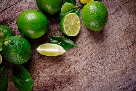 Photo pour Limes fraîches sur fond en bois - image libre de droit
