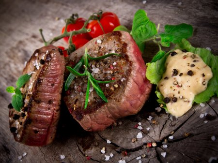 Photo for Medium grilled bbq steaks with fresh herbs and tomatoes - Royalty Free Image