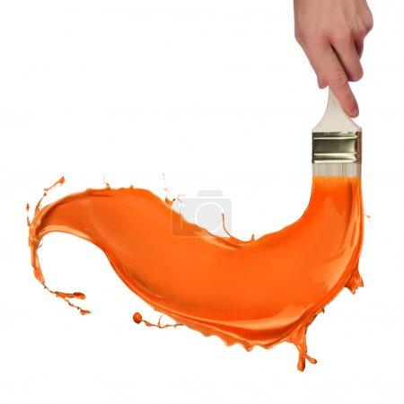 Photo for Orange paint splashing out of brush. Isolated on white background - Royalty Free Image