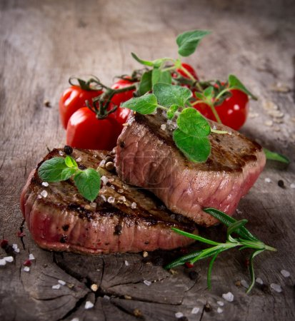 Photo for Grilled bbq steaks with fresh herbs and tomatoes - Royalty Free Image
