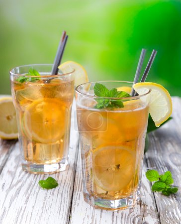 Photo for Glass of ice tea with ice-cubes on wooden table - Royalty Free Image