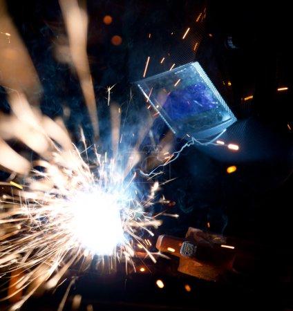 Photo pour Soudeur en action avec des étincelles brillantes. construction et fabrication thème. - image libre de droit