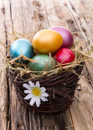 Photo for Easter colored eggs on hay, close-up - Royalty Free Image