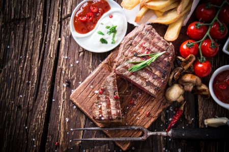 Photo for Delicious beef steak on wooden table, close-up - Royalty Free Image