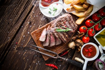 Photo for Tasty beef steak on wooden table with vegetable side-dish. - Royalty Free Image
