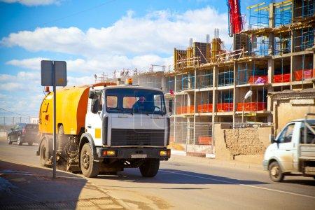 Photo pour La voiture nettoie la route de la poussière. la construction d'un bâtiment en arrière-plan - image libre de droit