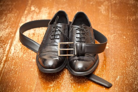 Classic black leather shoes and a leather belt with a buckle on the vintage background