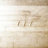 Tři sedmičky na dřevěné pozadí