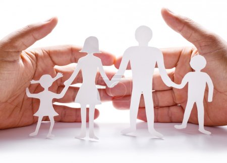 Photo pour Figures en carton de la famille sur fond blanc. Le symbole de l'unité et du bonheur. Les mains serrent doucement la famille . - image libre de droit