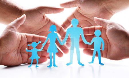 Photo for Cardboard figures of the family on a blue background. The symbol of unity and happiness. - Royalty Free Image