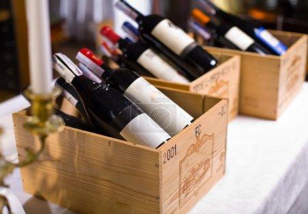 Foto de Botellas de vino en cajas de madera están en el restaurante table. - Imagen libre de derechos