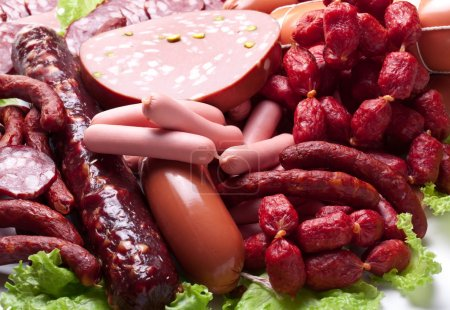 Meat and sausages on lettuce leaves.