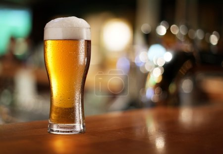 Photo for Glass of light beer on a dark pub. - Royalty Free Image