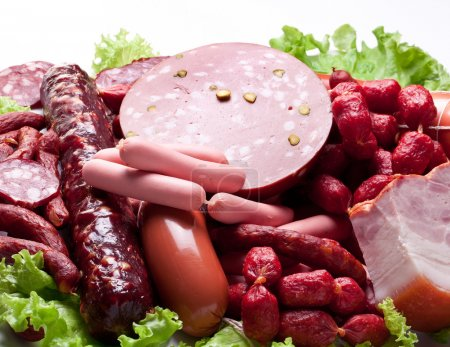 Meat and sausages on lettuce leaves. Isolated on w...