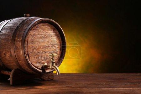 Foto de Barril de roble viejo sobre una mesa de madera. detrás de fondo oscuro borrosa - Imagen libre de derechos