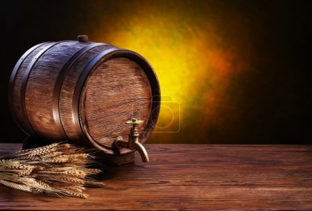Photo for Old oak barrel on a wooden table. Behind blurred dark background. - Royalty Free Image