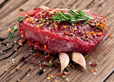 Photo for Raw beef steak on a dark wooden table. - Royalty Free Image