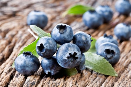 Photo for Blueberries with leaves on a old wooden table. - Royalty Free Image