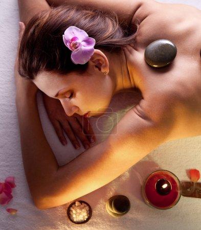 Woman getting stones spa procedures.