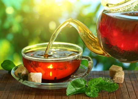 Photo for Pouring tea from a teapot into a cup on a blurred background of nature. - Royalty Free Image
