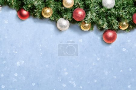 Christmas decoration with fir and baubles over snow.