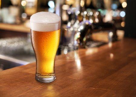Photo pour Verre à bière sur une barre de table. Closeup. - image libre de droit