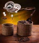 Cup of coffee, a sugar and coffee beans in the air .